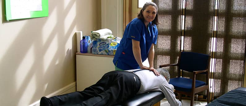 A student at the Naprapathic Doctorate School demonstrating technique on a patient's back.